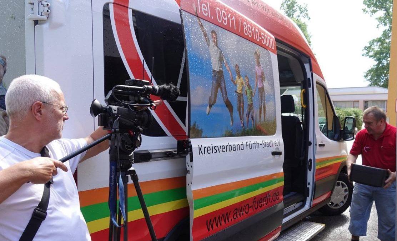 Kameramann vor AWO Bus mit Mitarbeiter (Dreharbeiten für Imagefilm)